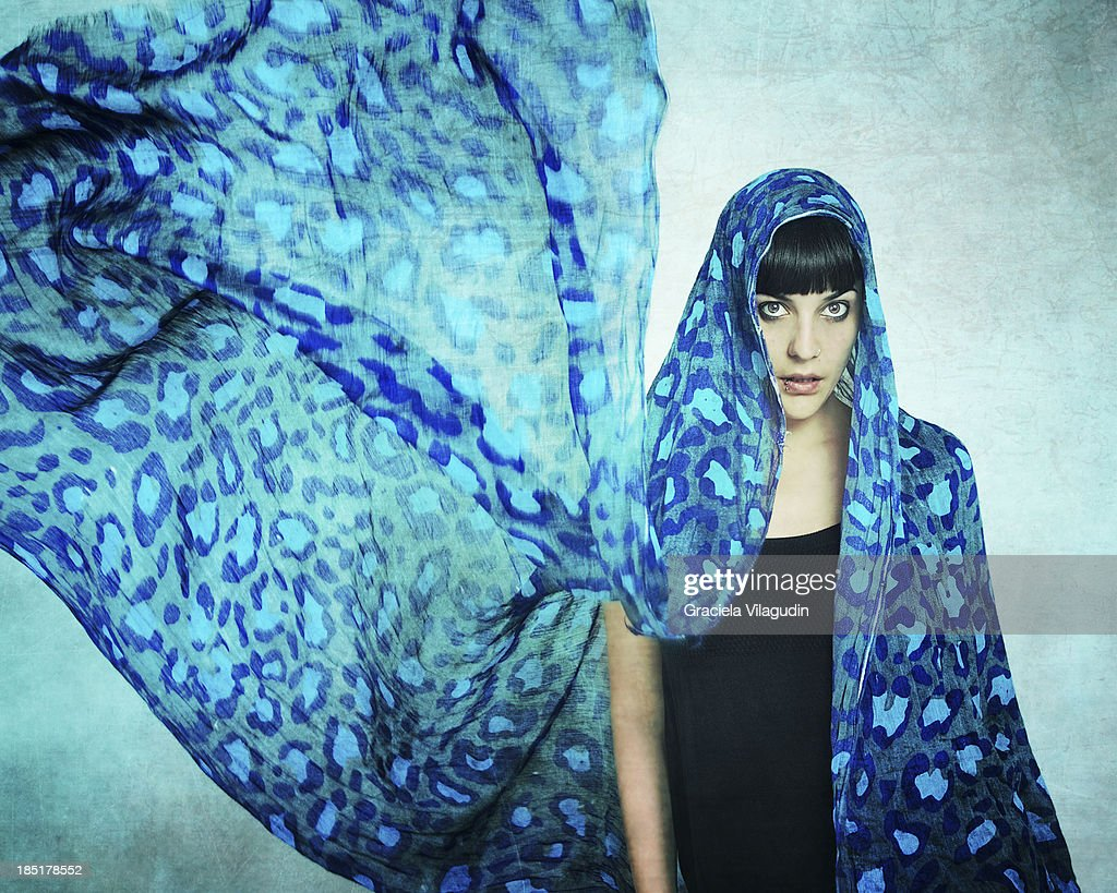 Girl with a blue scarf over her head flying : Stock Photo