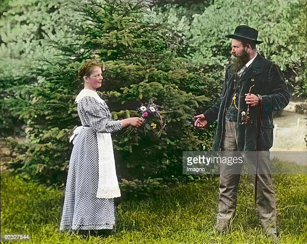 Girl with a bouquet and a big farmer dressed in traditional costume Austria Handcolored lantern slide Around 1910