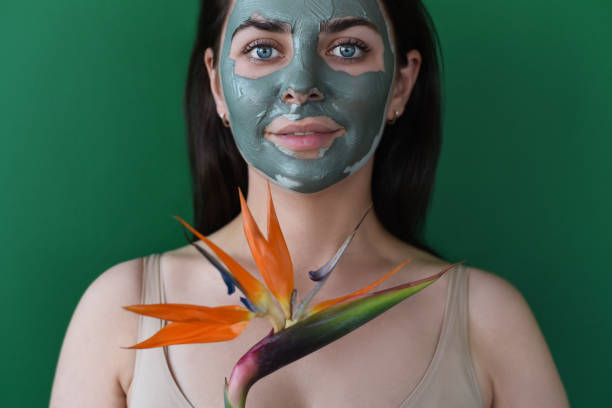 Girl with a clay mask on her face and a flower.