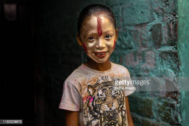 A girl with a coloured face seen posing for a photo during the celebration Holi known as the festival of colour is an ancient Hindu spring festival...