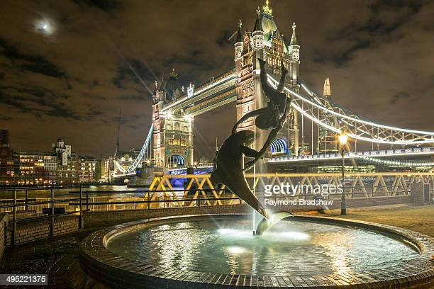 Girl With A Dolphin Fountain with the Tower Bridge in the background at night.