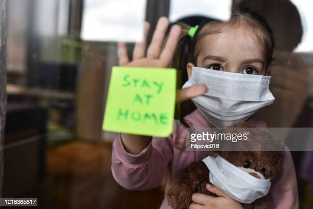 girl with a face maks standing and looking through the window and showing 'stay home' message - shielding stock pictures, royalty-free photos & images