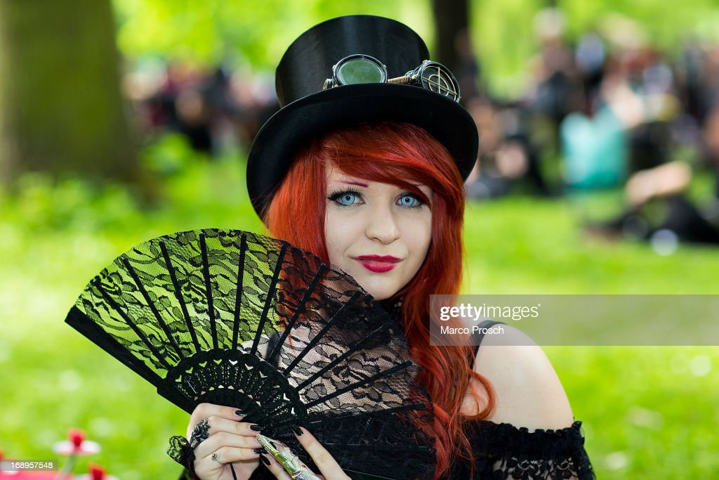 A girl with a fan attends the traditional park picnic on the first day of the annual Wave-Gotik Treffen, or Wave and Goth Festival, on May 17, 2013 in Leipzig, Germany. The four-day festival, in which elaborate fashion is a must, brings together over 20,000 Wave, Goth and steam punk enthusiasts from all over the world for concerts, readings, films, a Middle Ages market and workshops.