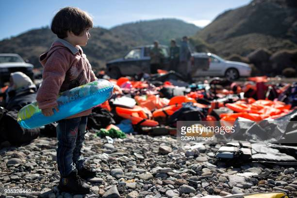 A girl with a flotation ring stands at the shore after arriving with dozens of other asylumseekers to a shore littered with lifejackets and other...