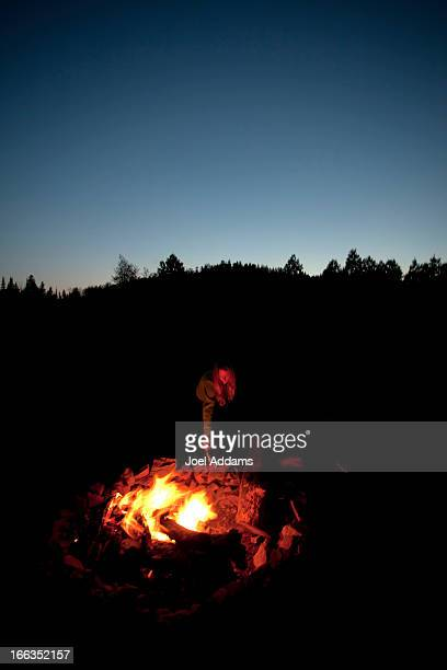 A girl with a headlamp stands next to a campfire.