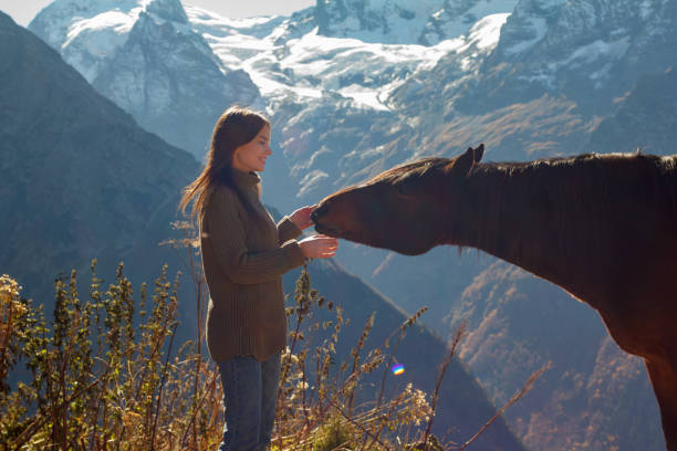 Girl with a horse in the background of mountains