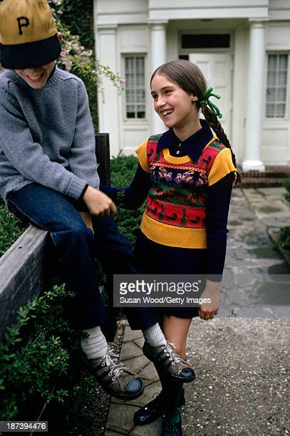 A girl with a knit tank top over a navy dress and a boy in a baseball cap grey sweater and jeans share a laugh at a fence in front of a school May...