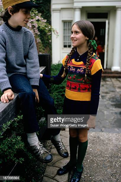 A girl with a knit tank top over a navy dress and a boy in a baseball cap grey sweater and jeans pose at a fence in front of a school May 1972 The...