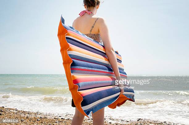 A girl with a Lilo at the beach