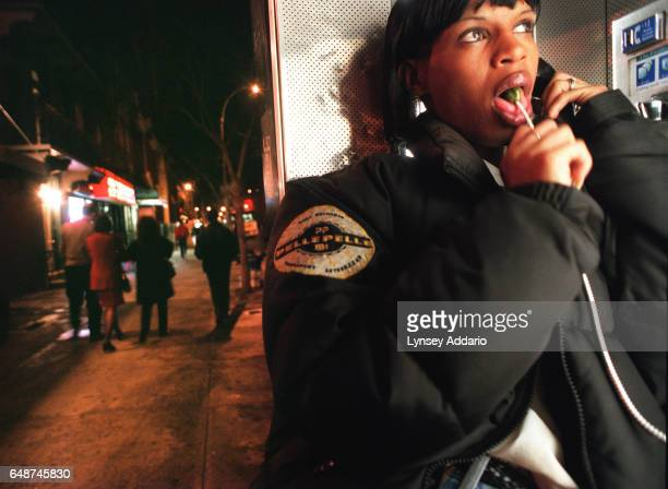 A girl with a lollipop speaks on pay phone while prostitutes wait for customers behind her in the West Village of New York CIty 1999