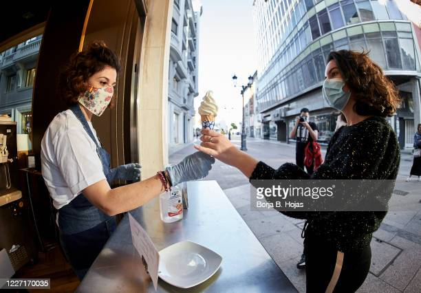 A girl with a mask buys an ice cream and is attended by a clerk with a mask and gloves following the protection measures against the Coronavirus at...