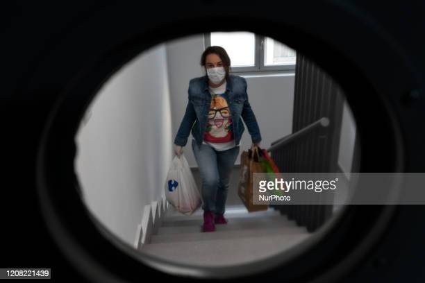 A girl with a mask returns home after buying food during the mandatory governmentordered quarantine of the coronavirus in Santander