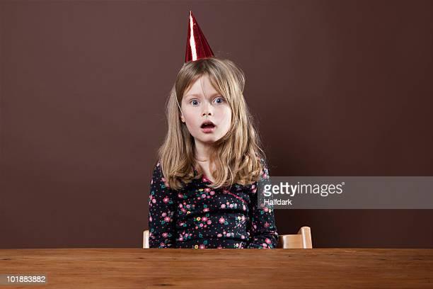 a girl with a party hat on staring in shock, studio shot - gorro de fiesta fotografías e imágenes de stock