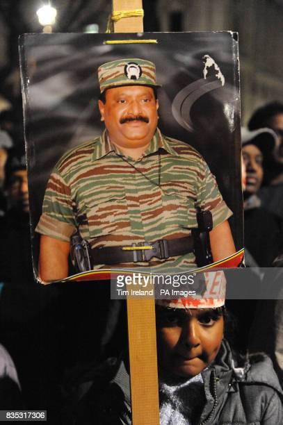 A girl with a portrait of Tamil Tiger leader Velupillai Prabhakaran watching over Prarameswaran Subramaniam and Sivatharsan Sivakumaraval students...