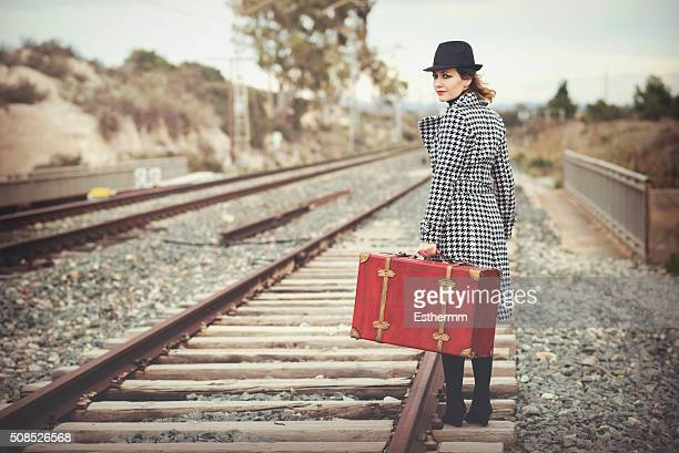 girl with a red suitcase sitting on the railroad tracks