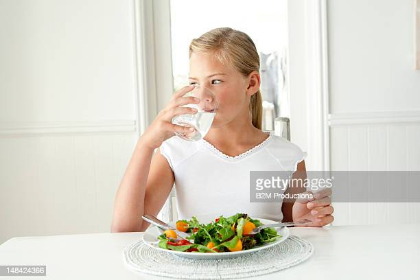 Girl with a salad drinking a glass of water