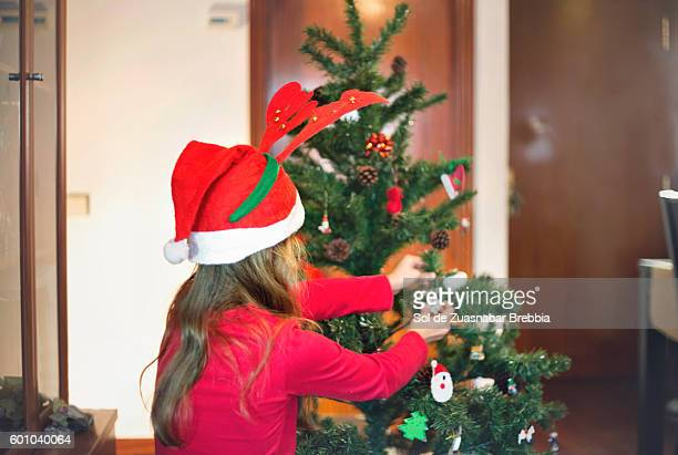 Girl with a Santa hat decorating a Christmas tree at home.