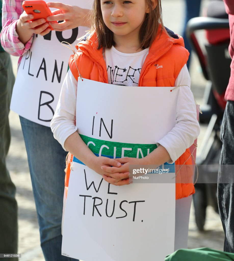 girl with a sign saying in science we trust some hundreds of