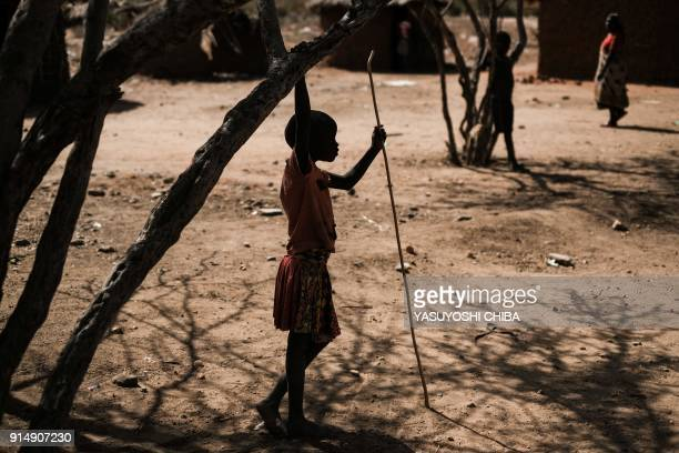 TOPSHOT A girl with a stick looks on in Alakas village where holds antifemale genital mutilation women group PERUR bordering with Kenya northeast...