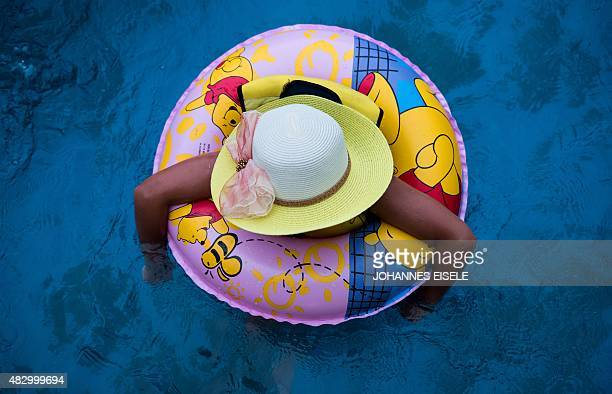A girl with a swimming ring cools down in a water park in Shanghai on August 5 2015 Typhoon Soudelor is set to bring an end to the heatwave affecting...