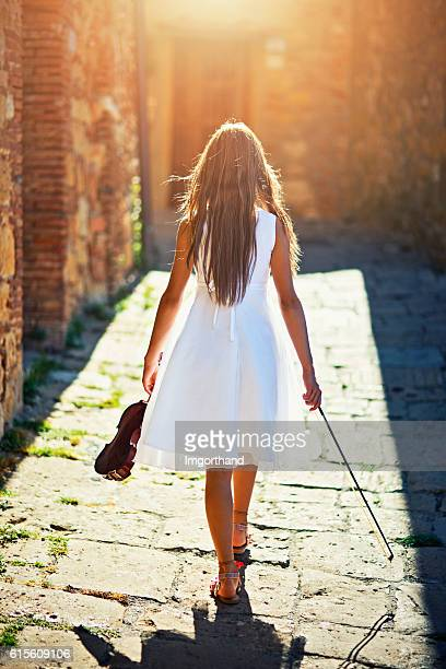 Girl with a violin walking in the sunny street