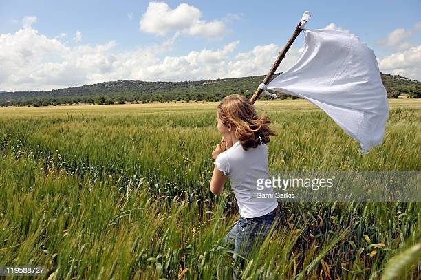 Girl with a white flag in wheat field
