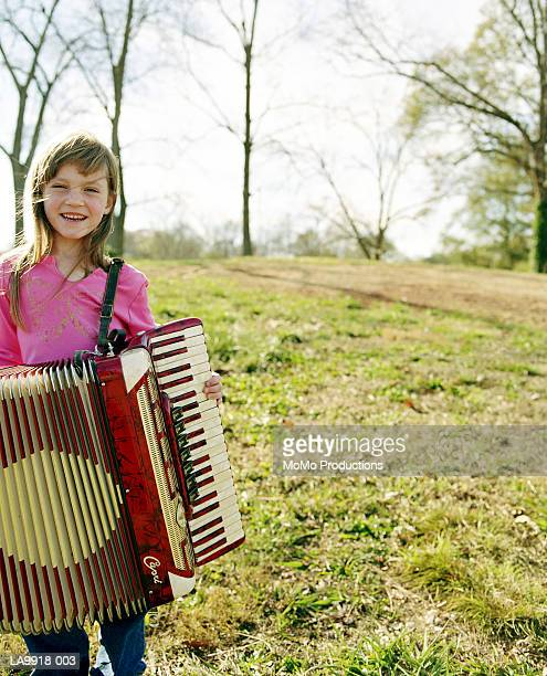 Girl (8-10) with accordion, outdoors