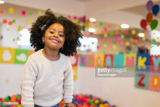 girl with afro hair and brown skin with an approximate age of 4 years looks at the camera for the photo and shows a beautiful smile while in the back we observe a pool of colored balls, letters, blobs of many colors - 4 5 years stock pictures, royalty-free photos & images