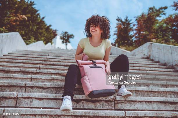 Girl With Afro Hairstyle Taking a Rest On a Staircase On a Sunny Day