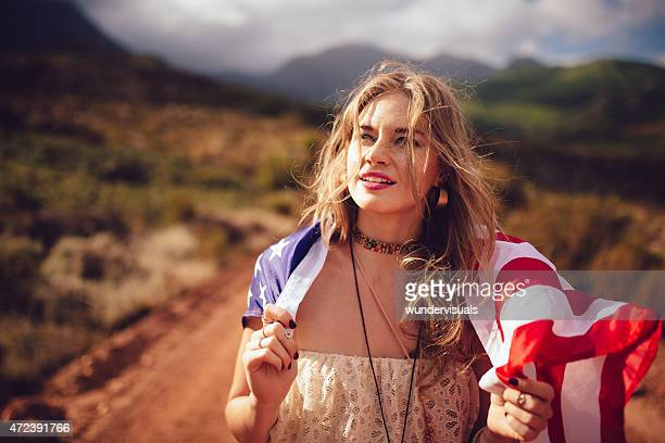 Girl with an American flag over her shoulders in countryside