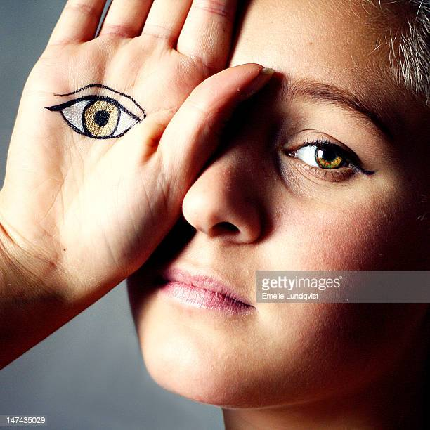 Girl with an eye painted on hand