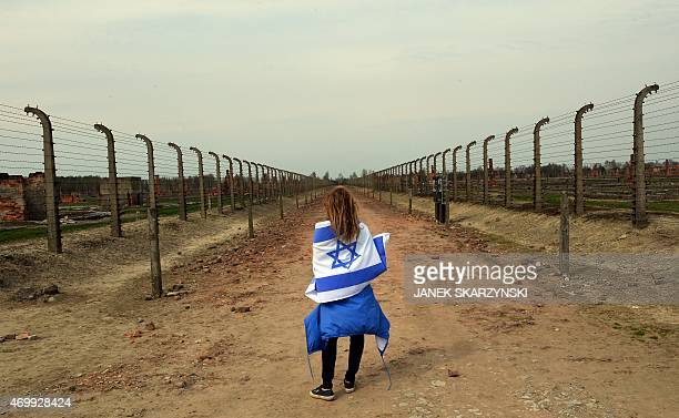 Girl with an Israeli flag stands in between a barbed wire fences in at the former Nazi German Auschwitz-Birkenau death camp during the 'March of the...