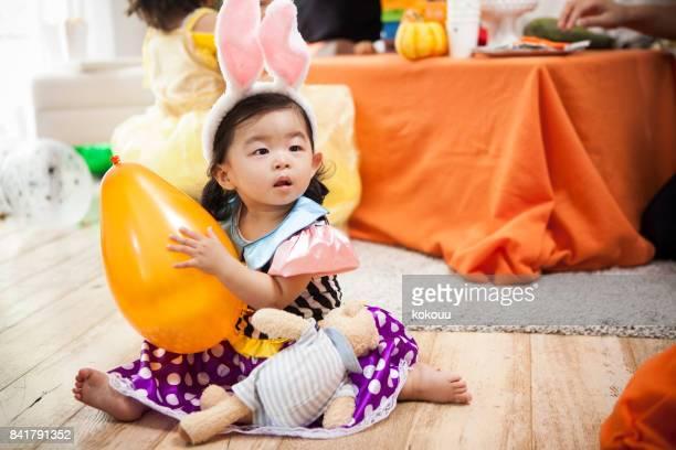 オレンジの風船を持つ少女は盲目の顔とどこか見ています。