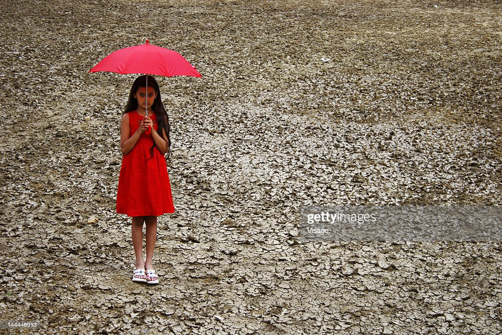 A girl with an umbrella on a dry land : Stock Photo