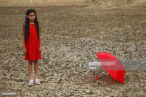 A girl with an umbrella on a dry land