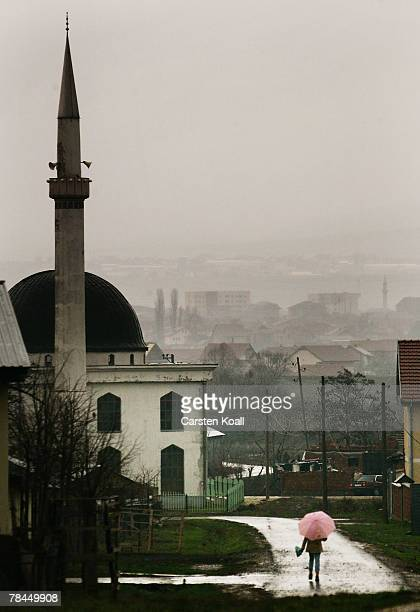 A girl with an umbrella passes the mosque on December 13 2007 in Polje near Pristina in breakaway province Kosovo Serbia The Serbian families from...