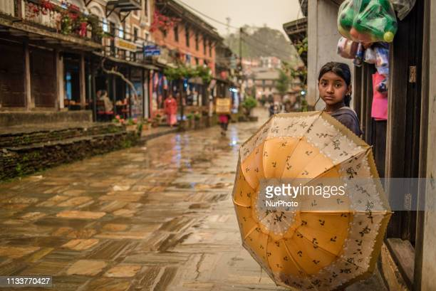 A girl with an umbrella stands on the main street of the old town in Bandipur Nepal on March 30 2019