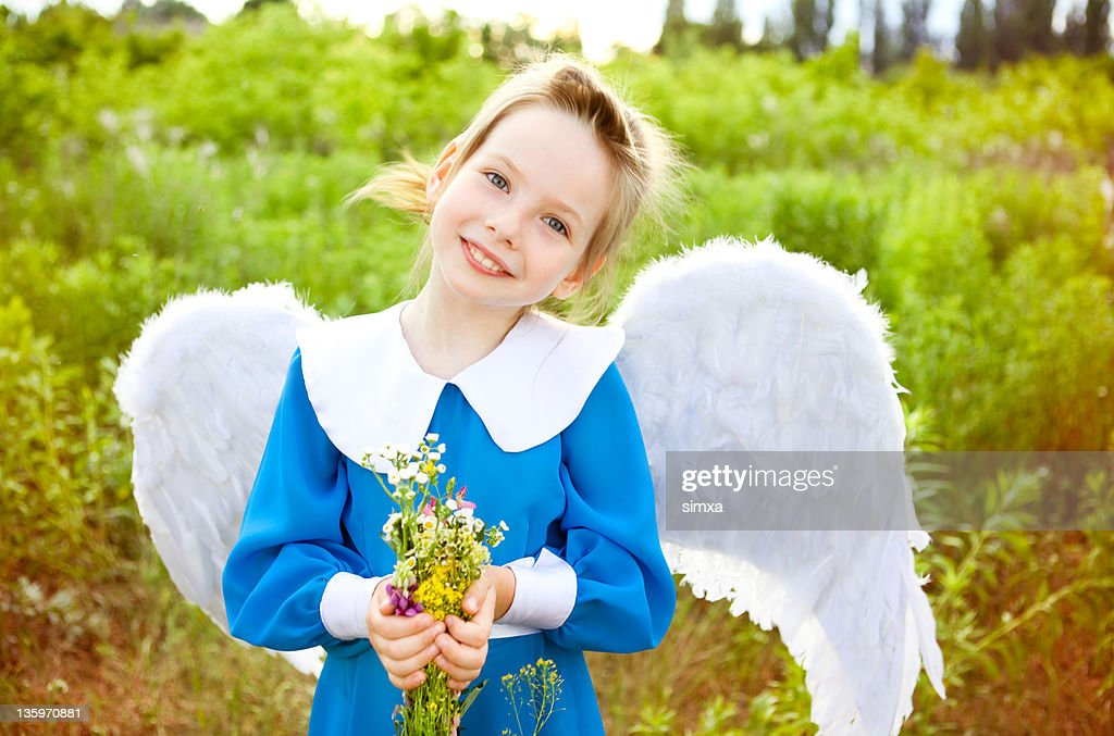 Girl with angel wings and bouquet of flowers : Stock Photo