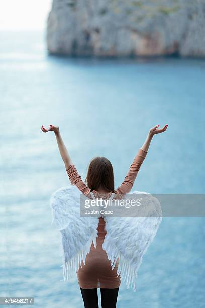girl with angel wings raising arms up by the sea