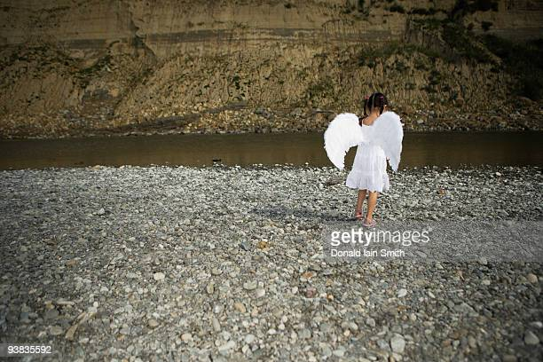 Girl with angel wings walks towards river