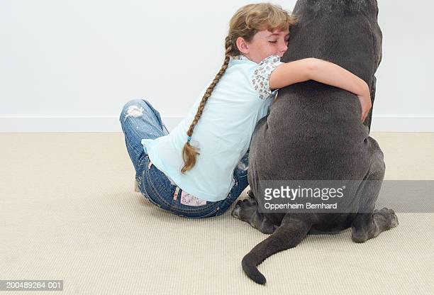 Girl (9-11) with arm around Great Dane, eyes closed