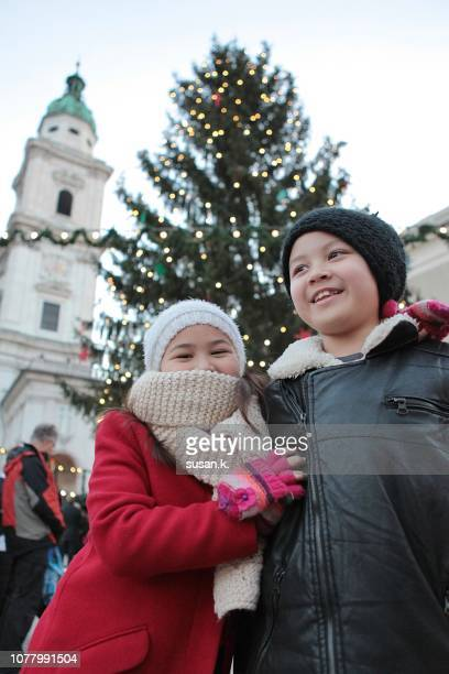 Girl with arm around her brother, both singing and laughing. - Naughty Christmas Ornaments Stock Photos And Pictures |