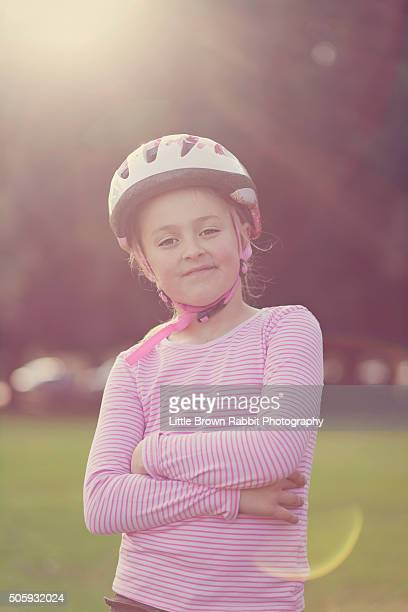 Girl with Arms Folded Wearing a Cycle Helmet.