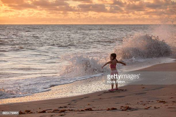 Girl with arms open whilst waves splash at sunrise, Blowing Rocks Preserve, Jupiter Island, Florida, USA