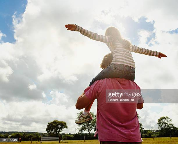 Girl (8-9) with arms outstretched, on fathers shoulders outdoors