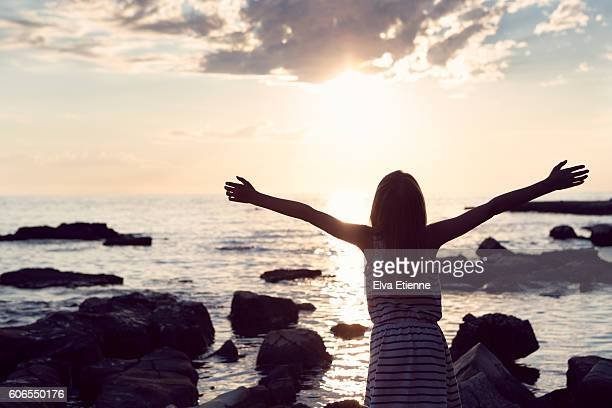 Girl with arms raised, as sun sets across sea