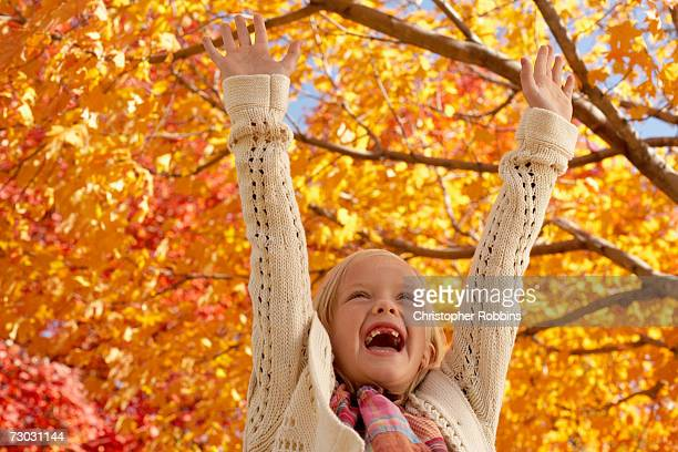 Girl (8-9) with arms raised, autumn trees in background, close-up, low angle view