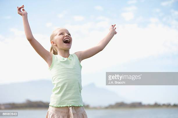 Girl with arms raised shouting at sky