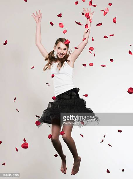 Girl (12-13) with arms up jumping, rose petals falling
