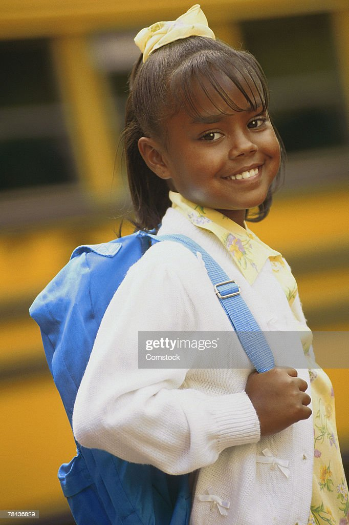 Girl with backpack by school bus : Stockfoto